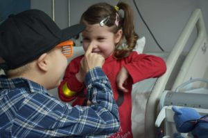 Choremu chłopcu pomaga siostrzyczka
